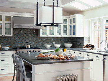 bright, functional kitchen space features a gorgeous backsplash with natural stone tiles